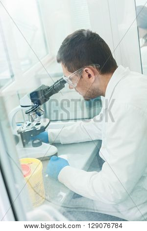 Professional young researcher is analyzing sample in laboratory. He is sitting at desk. Man is looking into the microscope seriously