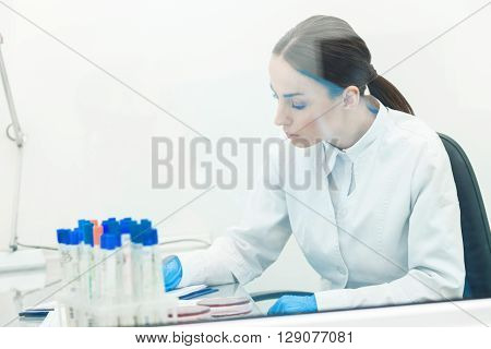 Cheerful young scientist is making notes with concentration in lab. Woman is sitting at desk near flasks