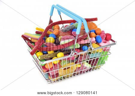 a metal shopping basket full of candies with different shapes and flavors on a white background
