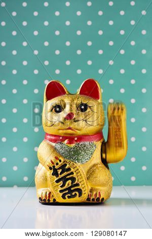 a golden chinese lucky cat with its left paw raised in motion, on a white surface against a green background patterned with white dots