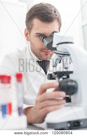 Professional male researcher is looking into the microscope with concentration. Man is sitting at desk in laboratory