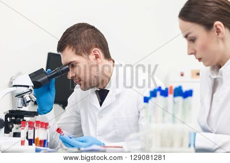 Skillful two researchers are analyzing samples in clinic. The man is holding a flask and looking into microscope with seriousness. Woman is sitting at desk near him