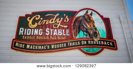Mackinaw Island, Michigan, USA - May 6, 2016: Advertisement for a riding stable on Mackinaw Island. The island has a ban on automobiles and traversing the island is done by foot, bike or horse.