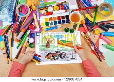 sport car racing child drawing, top view hands with pencil painting picture on paper, artwork workplace