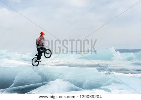 Girl jumping on a bmx on steep and dangerous ice.
