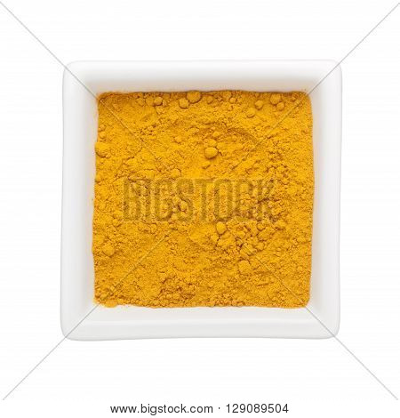 Turmeric powder in a square bowl isolated on white background