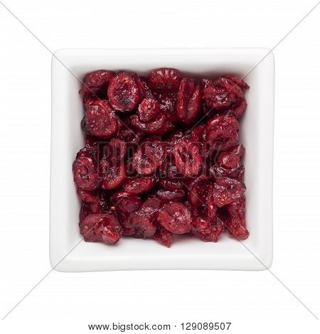 Dried cranberries in a square bowl isolated on white background