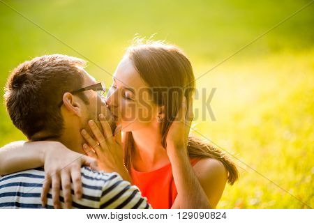 Romantic young couple hugging and kissing in nature