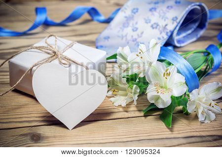 Gift Box, Flowers, Card, Ribbon And Tie On Wooden Table