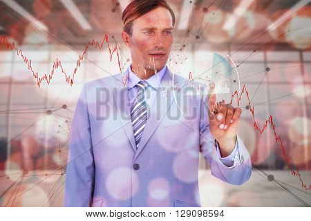 Handsome businessman touching invisible screen against modern room overlooking city