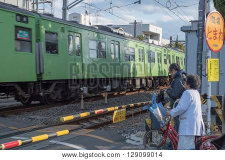Kyoto Japan-December 14 2015 : the old woman and man are waiting to cross the railroad