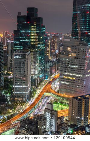 A shot from one of the high rises building in Tokyo which focuses on the illuminated expressway and the lights of the vehicle