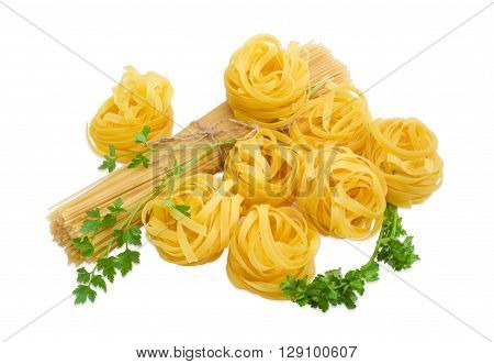 Uncooked dried egg pasta tagliatelle bunch of long pasta and two sprigs of parsley on a light background