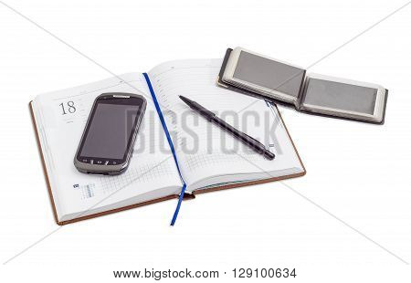 Mobile phone and black ballpoint pen on open business diary with blue page-marker ribbon and open wallet with business cards on a light background