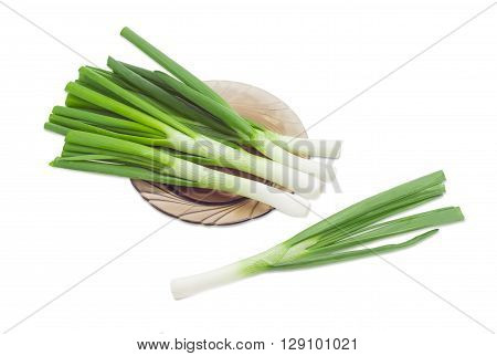 Several stalks of a green onion on a glass dish and one onion separately on a light background