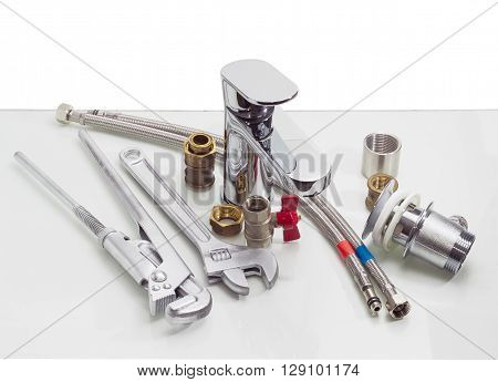 Single handle mixer tap plumber wrench adjustable wrench two hoses with metal braiding and another plumbing components on a reflective surface on a light background
