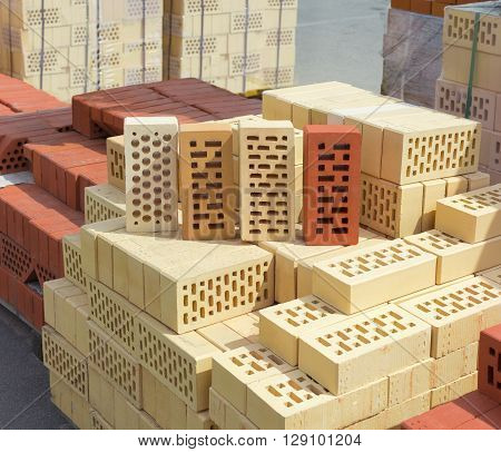 Several common perforated bricks of different colors and shapes of holes on a pallet with bricks on the background other pallets with bricks