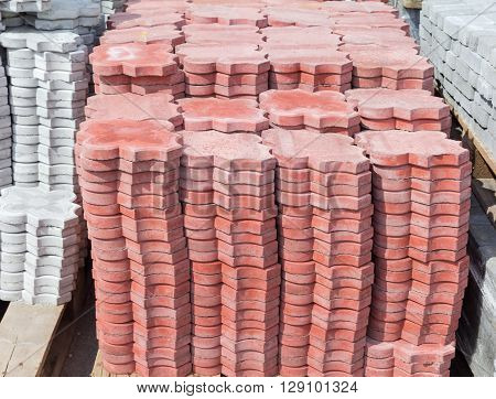 Red concrete pavement tiles with ornament made by vibration casting method stacked on a pallet on a warehouse