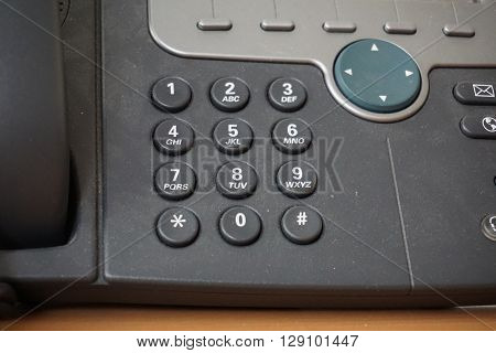 Dark telephone dial buttons of the land-line phone with numbers and letters together with a speed dial above them