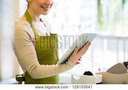 people, business, technology, sale and floristry and concept - close up of happy smiling florist woman with tablet pc computer at flower shop
