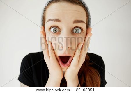 Stunned woman holding hands on her cheeks shocked with unexpected news. Isolated headshot of student girl looking in surprise mouth wide open astonished with some incredible news or sale prices