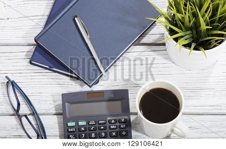mix of office supplies and gadgets on a wooden table background. view from above