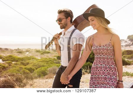 Portrait of a young cheerful couple walking holding hands. Boyfriend walking with his girlfriend and holding a guitar. Lovers going to the beach.