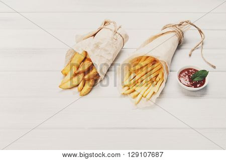 Potato wedges and french fries wrapped in brown wrapping paper. Fast food take away at white shabby chic wood. Fried potatoes with tomato sauce. Chips, potato slices. Top view, flat lay with copyspace