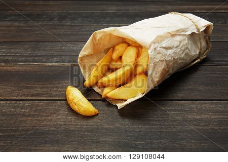 Tasty potato wedges wrapped into brown kraft wrapping paper. Fast food take away. Fried potatoes at rustic wooden boards background. Potatoes at wood. Fried chips, potato slices. Top view