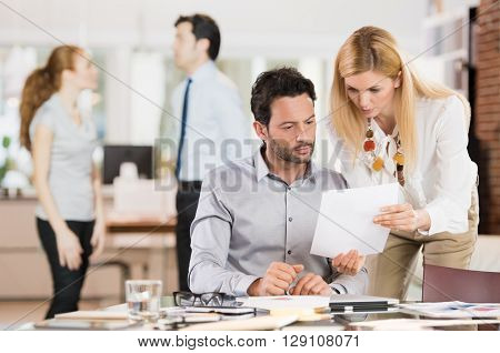 Young businesswoman sharing information with businessman. Young business woman explaining business reports to a coleague. Secretary delivered a document to a businessman.