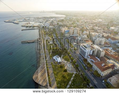 Aerial view of Molos Promenade on the coast of Limassol city in Cyprus. A view of the walk path surrounded by palm trees pools of water grass the Mediterranean sea piers rocks urban skyline old port and Marina.