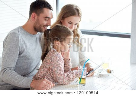 family, parenthood, technology and people concept - happy mother, father and little girl with tablet pc computer having dinner at restaurant