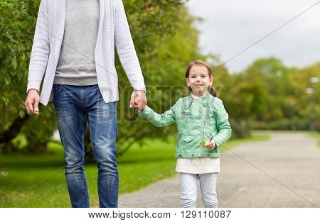 family, parenthood, fatherhood, adoption and people concept - close up of father and happy little girl walking in summer park