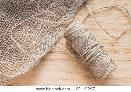 Burlap and skein jute twine on a wooden background.