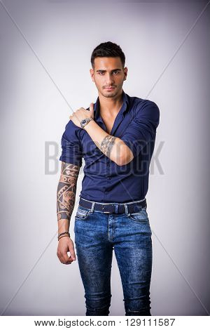 Handsome young man in blue shirt and jeans posing on grey background in studio