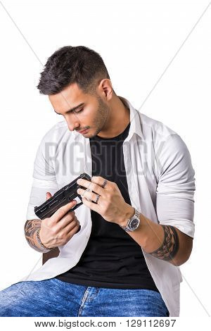 Young handsome man holding a hand gun, wearing black t-shirt, isolated on white background in studio