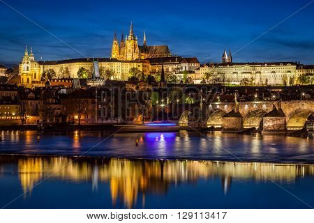 Prague Castle, Hradcany reflecting in Vltava river in Prague, Czech Republic at night. Charles Bridge to the right.