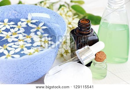 Adding essential oils to flower water in blue bowl. Aromatherapy bath.
