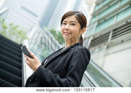 Young Businesswoman standing on escalator and use of cellphone