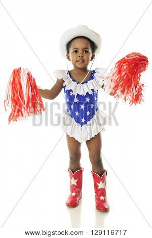 An adorable African American happy in her western, star studded red, white and blue outfit gently shaking her pom-poms.  On a white background.