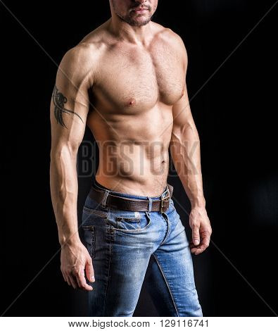 Unrecognizable young man with naked muscular torso, wearing jeans, isolated on black background