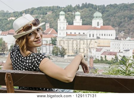 Young caucasian woman posing on the wooden bench with Saint Stephen's cathedral in Passau city Germany. Sexy brunette. Travel destination. Travelling theme. Beauty and fashion. Architectural theme.