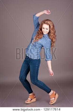 Young girl 20-22 year old having fun over gray in room. Wearing denim leggins and shirt.