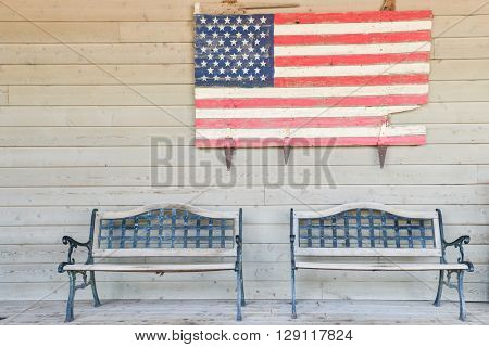 Rustic wooden log benches side by side against a wall of wooden siding with the flag of the United States of America hanging above the benches.