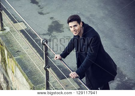 Sad brunet in black clothes looking down while standing near railing outdoors.