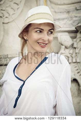 Young romantic woman posing in outdoor with white sunhat. Beauty and fashion. Female portrait. Sexy woman. Positive emotions.