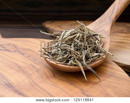 Silver tips white tea in the olive tree wooden spoon on the olive tree wooden board