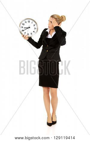 Young businesswoman terrified looks at the clock