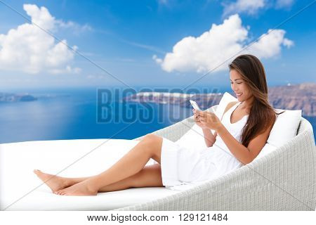 Asian woman using phone app relaxing on daybed on outdoor terrace. Home living outside patio furniture. Young adult texting on smartphone lying on sofa with Oia Santorini background enjoying summer.