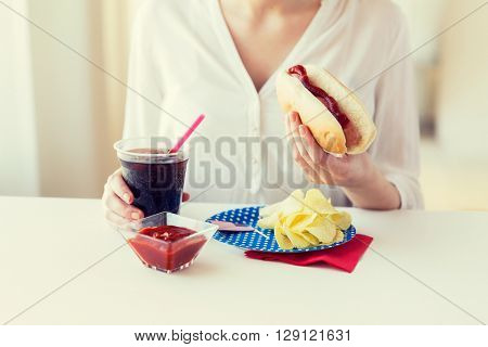 american independence day, celebration, patriotism and holidays concept - close up of woman hands holding hot dog and cola in plastic cup with potato chips and ketchup on 4th july at home party